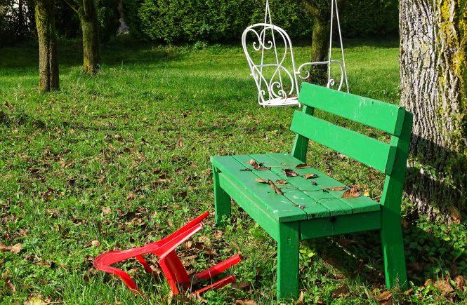 Eine grüne Bank steht neben einem Baum und ein roter Plastikstuhl liegt daneben