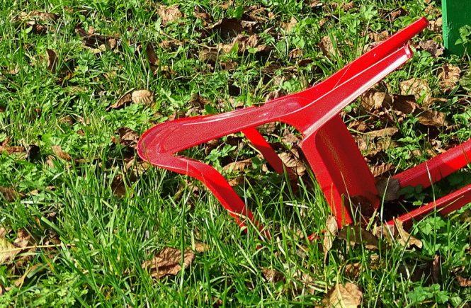 ein roter Stuhl der umgefallen in der Wiese liegt