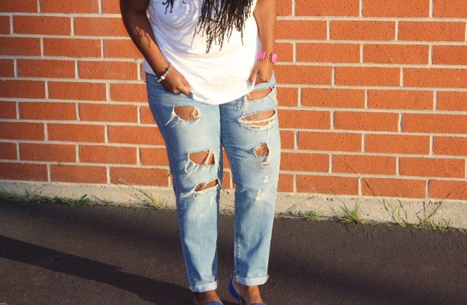 Eine Frau mit einer zerstörten Jeans vor einer Ziegelwand