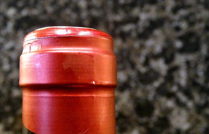Vor einer Granitwand steht eine Flasche mit einem roten Verschluss