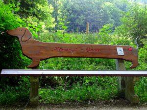 Ein Dackel-Bankerl, die Rückenlehne ist wie ein langer Dackel geformt. Am Po von dem Dackel gibt es ein Herz und das Schwanzerl ist aus Metall geformt.