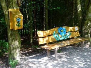 Eine Holzbank, auf der ein schöner blauer Enzian aufgemalt ist. Daneben hängt an einem Baum ein Briefkasten, wo ebenfalls ein Enzian aufgemalt ist.