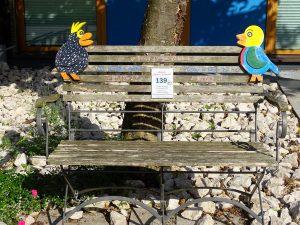 Ein kleines hölzernes Gartenbankerl, wo oben links und rechts je ein buntbemalter Holzvogel sitzt.