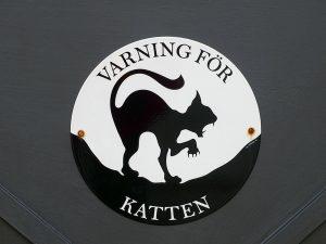 Ein rundes Schild, wo in Scherenschnitt eine übelgelaunte Katze steht. Auf dem Schild steht auf dänisch oder schwedisch Warnung vor der Katze.