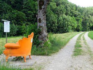 Auf der linken Seite des Bildes befindet sich ein ganz orange bemalener Sessel. Dahinter geht eine Schotterstraße vorbei und ein Baum steht daneben.