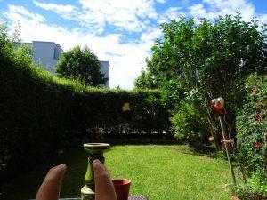 Der Blick von meiner Terrasse auf den Minigarten. Im Vordergrund Deko-Material und rotes Herz am Rosenstock. Im Hintergrund das Nachbarhaus und blauer Himmel mit Schäfchenwolken.
