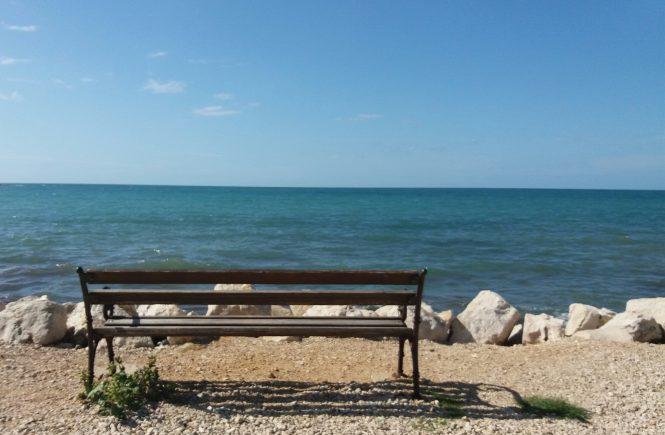 Ein Bankerl von hinten fotografiert mit dem Blick aufs Meer und den blauen Himmel