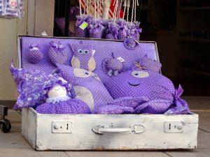 Ein weißer Koffer mit verschiedenen Stofftieren in violett und mit Lavendel gefüllt.