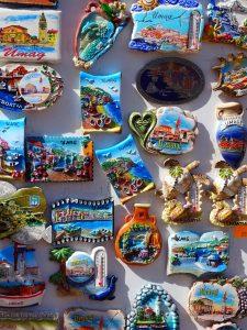 Eine Wand mit Magneten von Urlaubsdestinationen und verschiedenen Motiven
