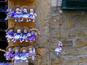 Kleine Puppen mit Strohhut und violettem Kleid auf einem Holzregal