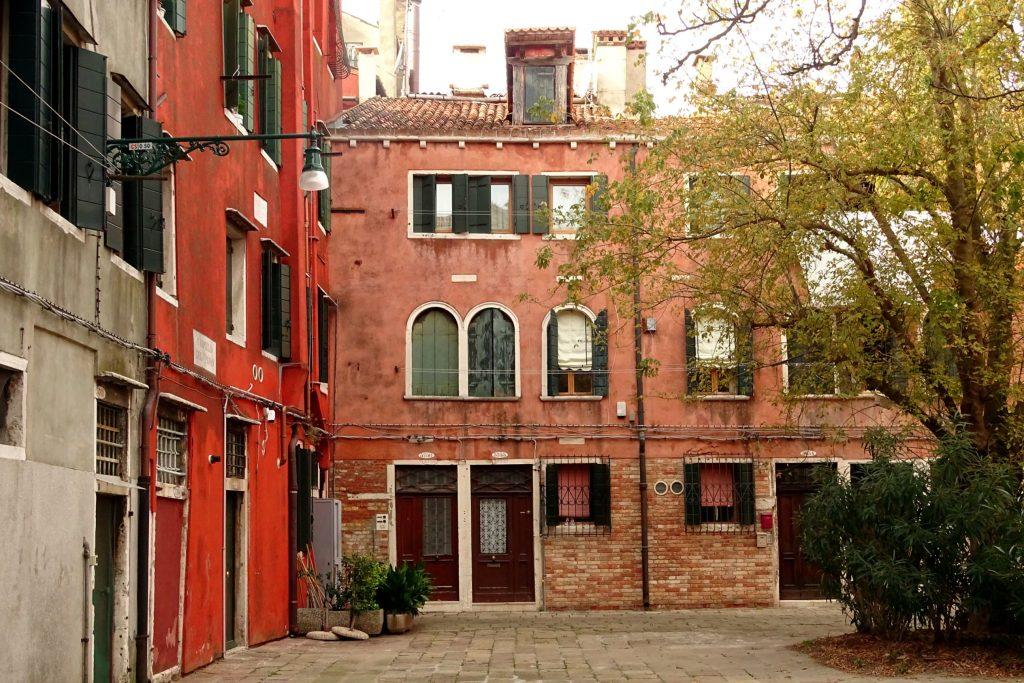 rote Fassaden von Häusern auf dem Platz in Venedig, wo die Bänke stehen