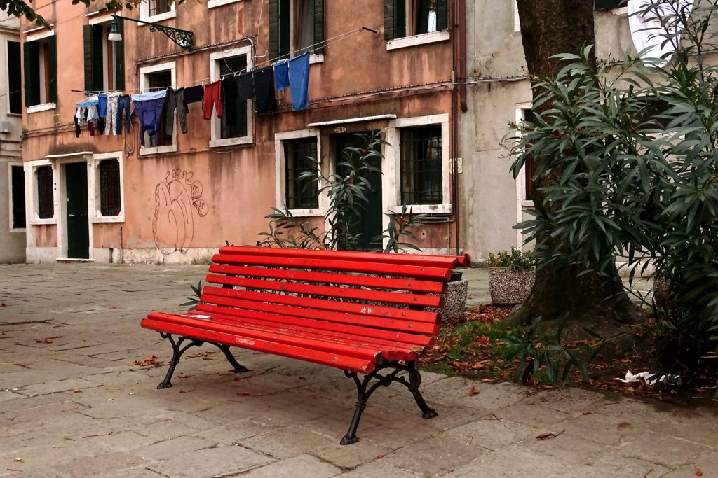 eine rote alte Bank auf einem kleinen Platz mitten in Venedig