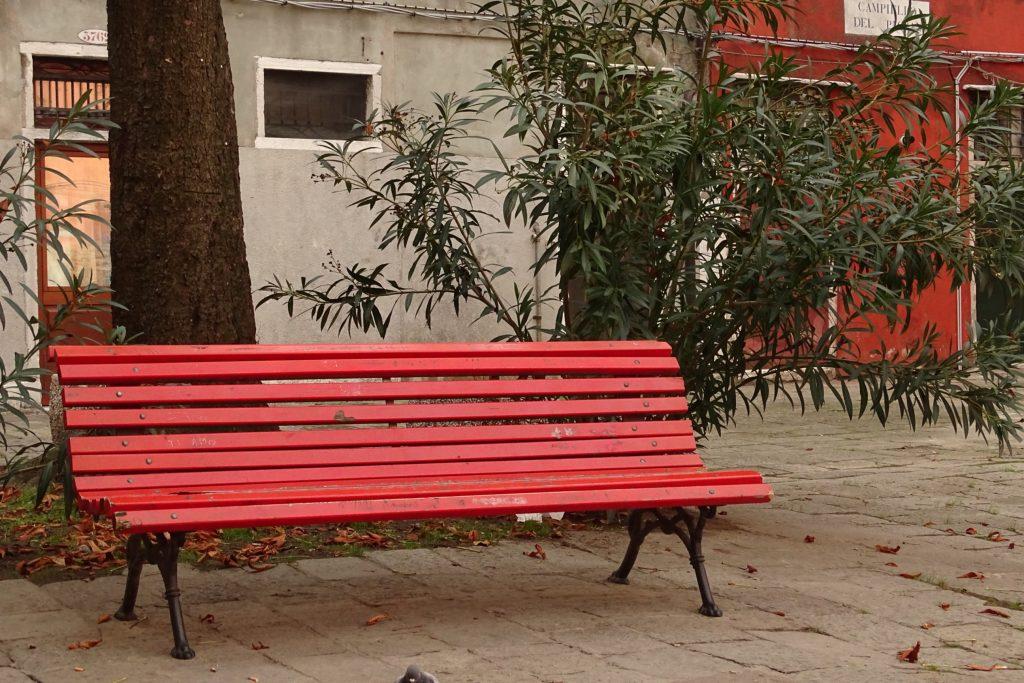 eine rote, alte Bank steht auf einem kleinen Platz in Venedig