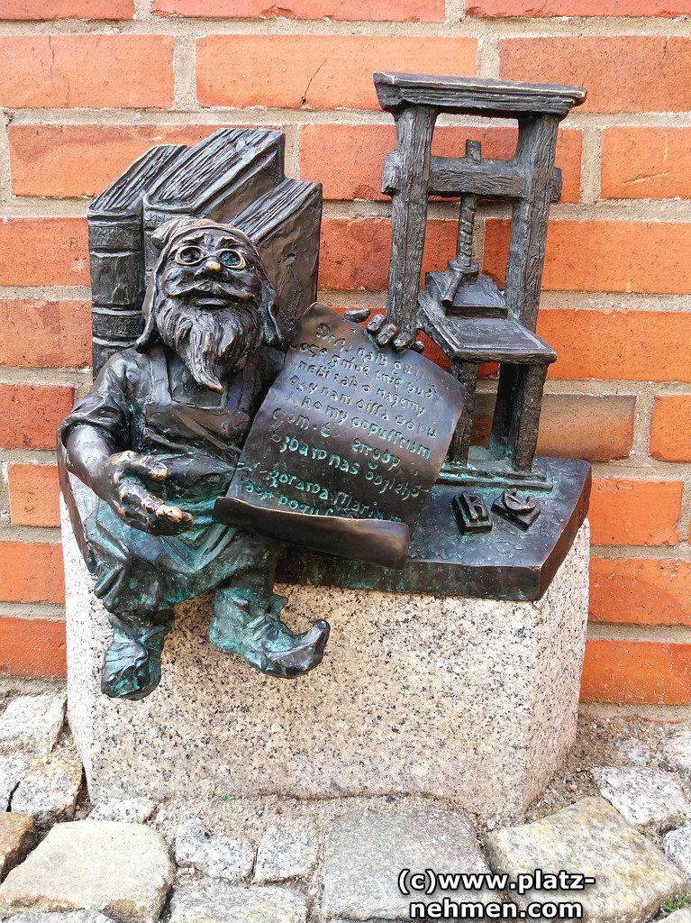 Der Buchdrucker Zwerg sitzt auf einem Sockel und lehnt an einigen Büchern. In der Hand hat er ein Papier mit Text. Im Hintergrund die Buchpresse.