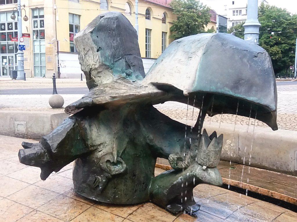 Ein Zwerg mit riesigem Hut hält seinen Schirm über den Froschkönig in einem Brunnen