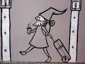 Es ist ein gemalter Zwerg in Grautönen, der seinen Koffer nachzieht und einen Becher to go in der anderen Hand hat.