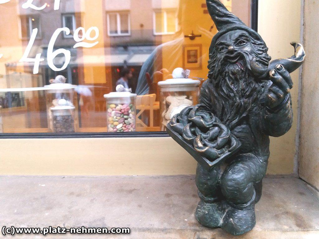 Ein Zwerg sitzt vor einem Schaufenster und bietet Kipferl an. Eines hält er in der linken Hand und der rechten Hand hat er ein Tablett voll Kipferl