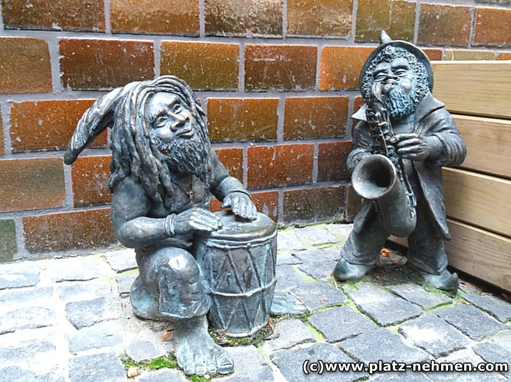 Zwei Zwerge als Musikanten, einer mit Dreadlocks und Trommel. Der andere spielt Saxophon und hat einen Vollbart
