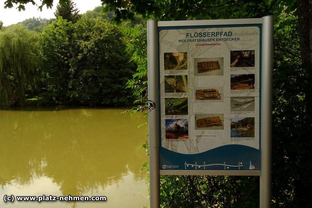 Der Fluß Loisach im Hintergrund mit Bäumen und im Vordergrund ein Bild, dass über den Flößerpfad informiert