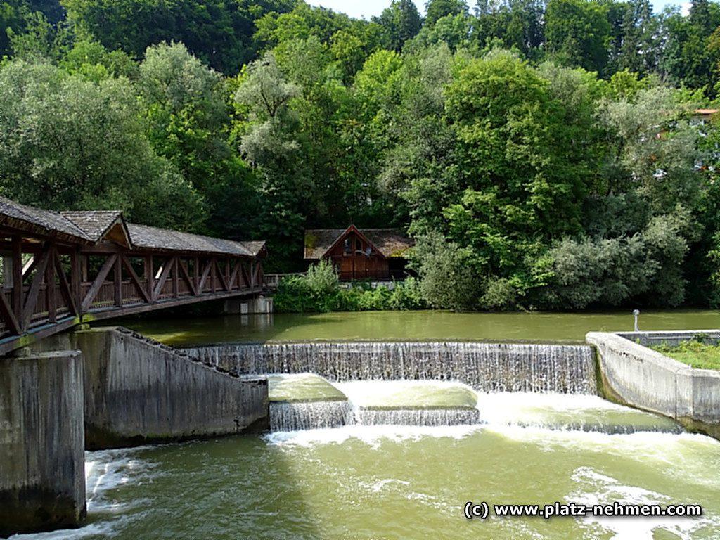 Kastelmühlwehr mit deer Loisach und der Holzbrücke mit Holzhaus im Hintergrund