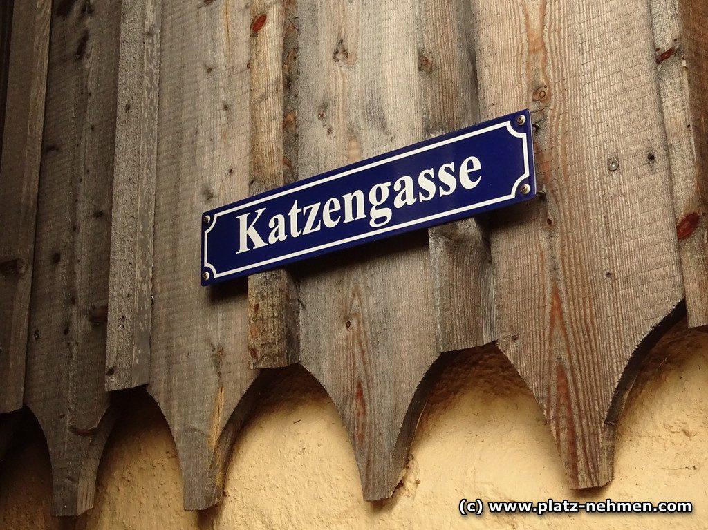 Eine Holzfassade auf der ein blaues Schild mit Katzengasse hängt