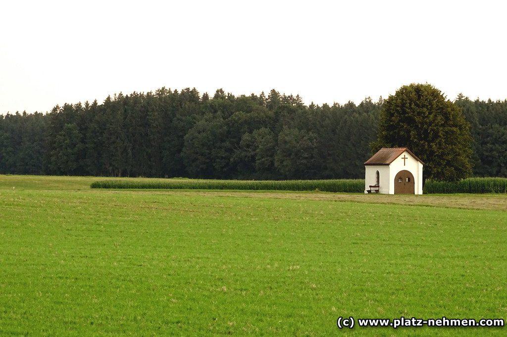 Grünes Feld und im Hintergrund der Wald. Dazwischen eine kleine Kapelle mit einem Bankerl davor